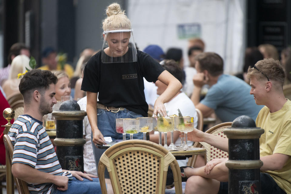 CARDIFF, WALES - AUGUST 08: A woman wearing a face visor serves drinks at Gin and Juice gin bar on August 08, 2020 in Cardiff, Wales. Coronavirus lockdown measures continue to be eased as the number of excess deaths in Wales falls below the five-year average. UK Prime Minister Boris Johnson has indicated he would force pubs, restaurants and shops to close ahead of schools in the event of severe coronavirus flare-ups. (Photo by Matthew Horwood/Getty Images)