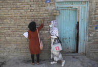 A health worker makes a mark on the door of a house after vaccinating the children of the family during a polio campaign in the old part of Kabul, Afghanistan, Tuesday, June 15, 2021. Gunmen on Tuesday targeted members of polio teams in eastern Afghanistan, killing a number of staffers, officials said. (AP Photo/Rahmat Gul)