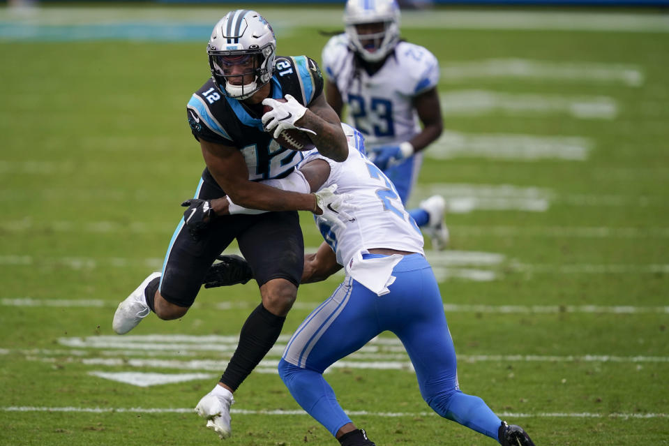 Carolina Panthers wide receiver D.J. Moore is tackled by Detroit Lions strong safety Duron Harmon during the second half of an NFL football game Sunday, Nov. 22, 2020, in Charlotte, N.C. (AP Photo/Gerry Broome)
