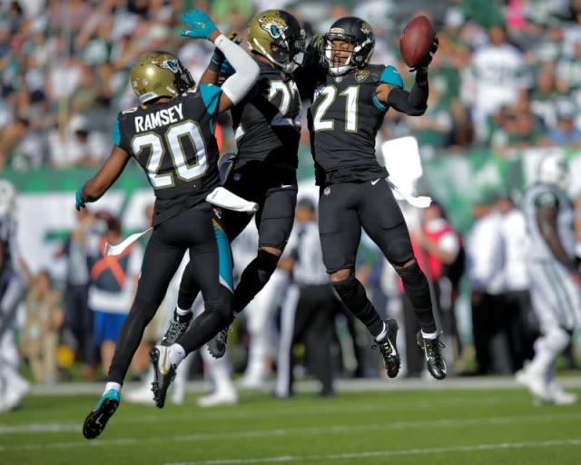 Jacksonville Jaguars players Jalen Ramsey, Aaron Colvin, and A.J. Bouye celebrate an intersection against New York Jets during their NFL football game in East Rutherford