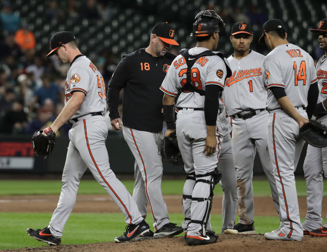 Baltimore Orioles pitcher Evan Phillips, left, is pulled by manager Brandon Hyde, second from left, during the seventh inning of the team's baseball game against the Seattle Mariners, Thursday, June 20, 2019, in Seattle. (AP Photo/Ted S. Warren)