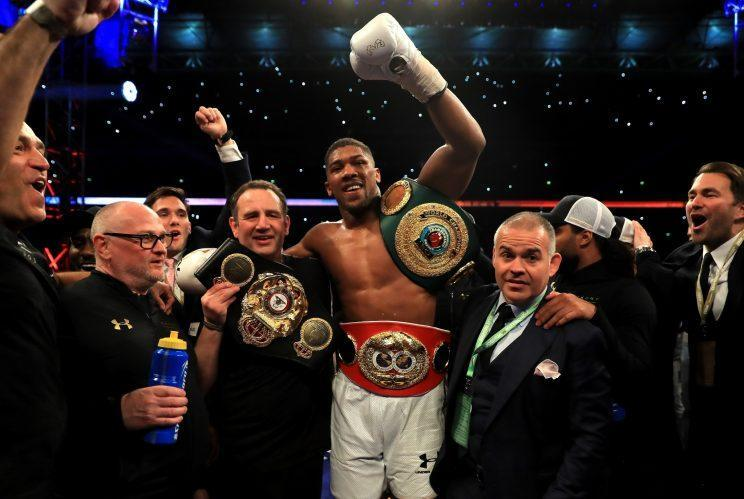 Anthony Joshua celebrates with his belts after stopping Wladimir Klitschko in the 11th round before 90,000 fans Saturday in the IBF-WBA heavyweight title fight at Wembley Stadium in London. (Getty Images)