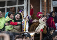 Relatives and family members cry near the coffin of elected official Riyaz Ahmad in Sopore, 55 kilometers (34 miles) north of Srinagar, Indian controlled Kashmir, Monday, March. 29, 2021. Gunmen killed an elected official of India's ruling party and a policeman in disputed Kashmir on Monday, police said. Police blamed anti-India militants for the attack. None of the rebel groups that have been fighting against Indian rule since 1989 immediately claimed responsibility for the attack. (AP Photo/Mukhtar Khan).