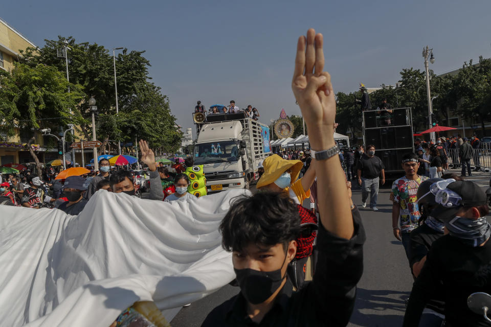 Students led pro-democracy protesters flash three-finger salute as they march to the Democracy Monument in Bangkok, Thailand, Saturday, Nov. 14, 2020. (AP Photo/Sakchai Lalit)