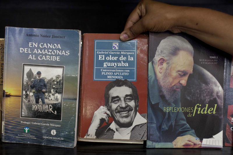 A woman shows a book by Colombian author Gabriel Garcia Marquez for sale next to a book by Fidel Castro at a state-run bookstore in Havana, Cuba, Thursday, April 17, 2014. Garcia Marquez, who died at his home in Mexico City on Thursday, became a hero to the Latin American left as an early ally of Cuba's revolutionary leader Fidel Castro. (AP Photo/Franklin Reyes)