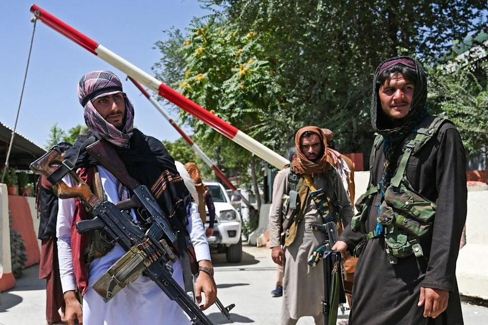 Taliban fighters stand guard along a roadside near the Zanbaq Square in Kabul on August 16, 2021, after a stunningly swift end to Afghanistan's 20-year war (AFP via Getty Images)