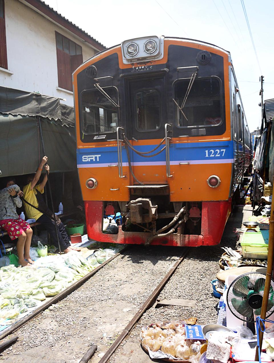 "<b>Maeklong railway market</b><br><br><p><b>A marketplace with a working railway track through it.</b></p><br><br><p>If you're driving from Bangkok to Hua Hin (which takes about 2.5 hours), make sure you schedule a stop in Maeklong Railway Market in Samut Songkhram, some 60km away from the capital. Locals call it Talad Rom Hoop Market, which translates to ""Market Umbrella Pulldown"" but tourists call it Scary Market (read on to find out why). At first glance, it looks like any typical open-air market in Thailand. The market is filled with stalls displaying juicy fruits, fresh vegetables, a variety of spices, herbs, seafood and plenty more. </p>"