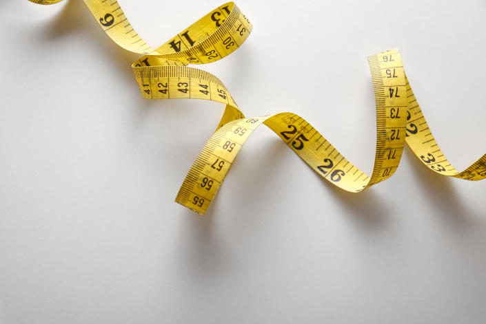 Yellow tape measure in meters and inches in a spiral on white table. Top view. Horizontal composition.