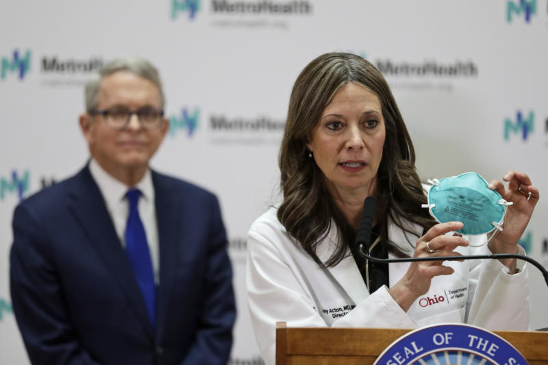 """FILE - In this Feb. 27, 2020 file photo Ohio Department of Health Director Amy Acton speaks during a news conference at the MetroHealth Medical Center in Cleveland. Ohio Gov. Mike DeWine, left, watches. Under pressure from law enforcement, Tennessee's top health officials quietly agreed in April to release the names and addresses of those who had been treated or exposed to COVID-19 to police departments and sheriff's offices. Acton issued an order April 24 requiring local health departments to provide emergency dispatchers the names and addresses of people within their jurisdictions who tested positive. The order required dispatchers to treat the data as """"protected health information"""" and to remove it from the system once a person has recovered from the illness, although the order is unclear on how dispatching agencies would learn of this follow-up information. (AP Photo/Tony Dejak, file)"""