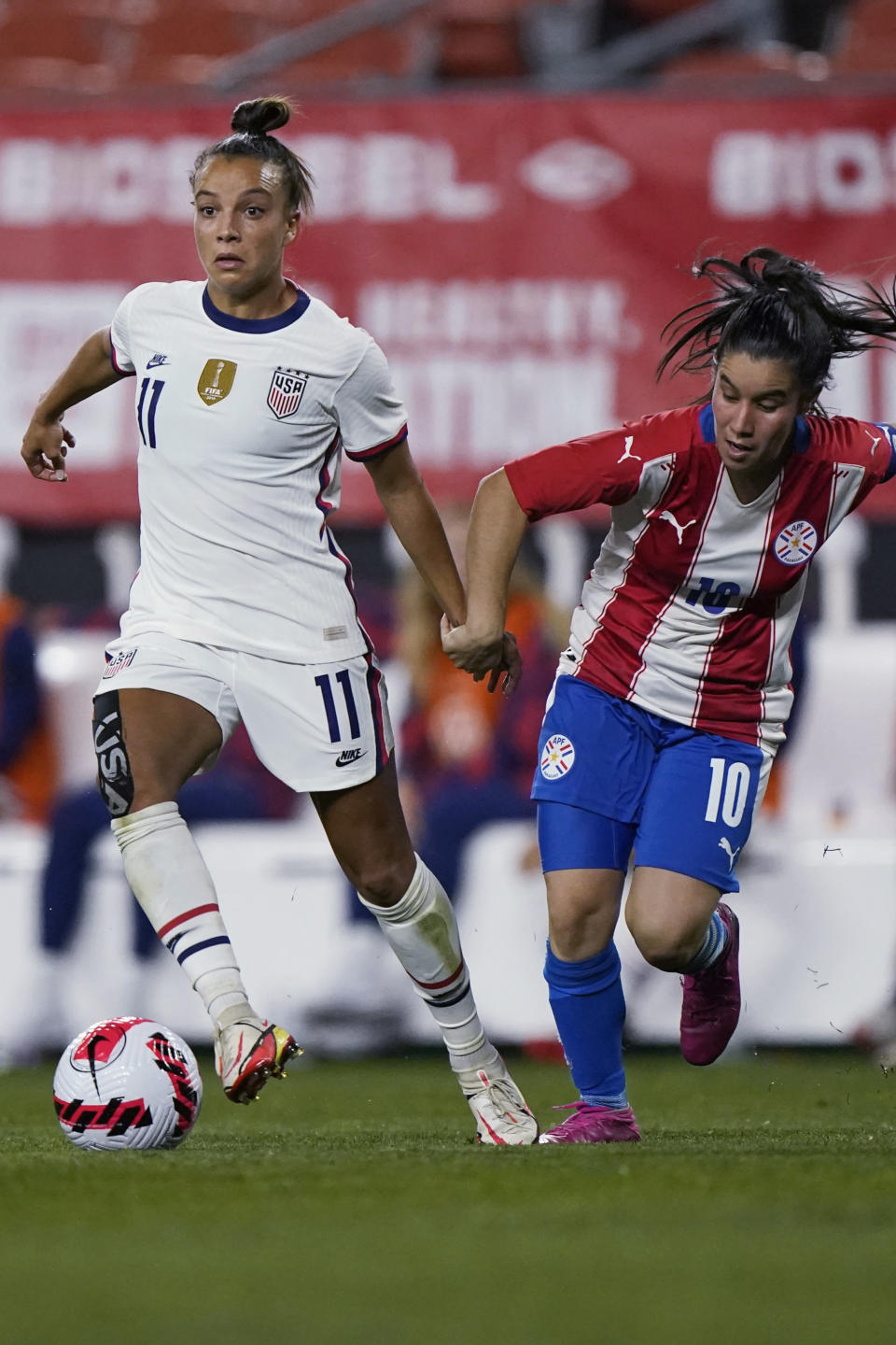 U.S. forward Mallory Pugh (11) moves the ball past Paraguay midfielder Fanny Godoy (10) during the second half of an international friendly soccer match, Thursday, Sept. 16, 2021, in Cleveland. The United States won 9-0. (AP Photo/Tony Dejak)