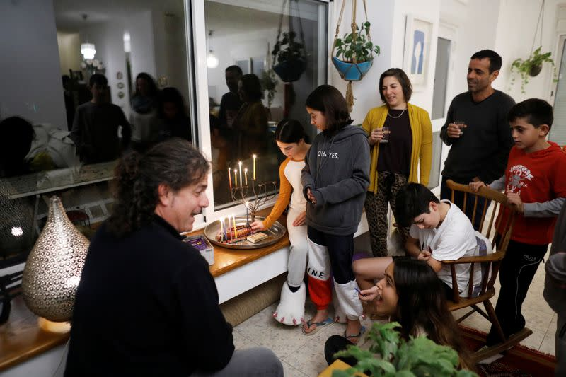 Members of the Ben Shahar family light a hanukkiyah, a candlestick with nine branches that is lit to mark Hanukkah, the 8-day Jewish Festival of Lights, in Moshav Kfar Mordechai, Israel