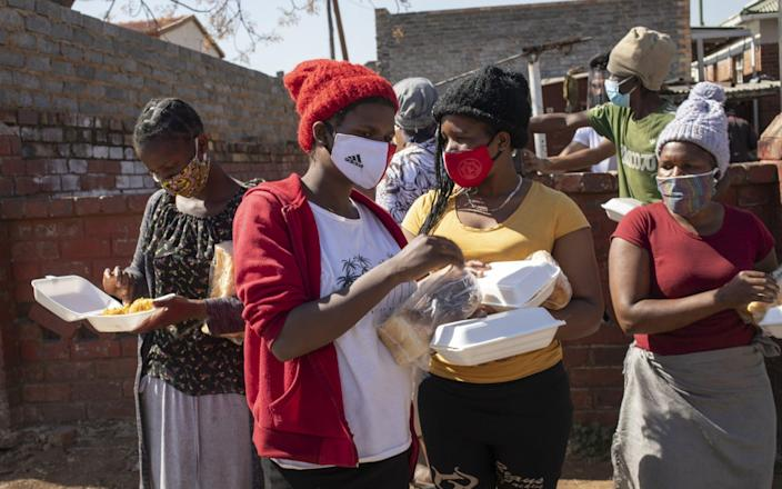 Women receive bread at a food handout during the Eid al Adha at the 'Hunger Has No Religion' feeding scheme, in Johannesburg - KIM LUDBROOK/EPA-EFE/Shutterstock/Shutterstock