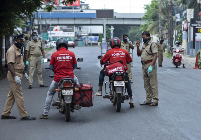 Policemen check the credentials of food delivery personnel during a lockdown imposed to curb the spread of coronavirus in Kochi, Kerala state, India, Saturday, May 8, 2021. Kerala, which emerged as a blueprint for tackling the pandemic last year, began a lockdown on Saturday. (AP Photo/R S Iyer)