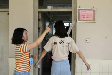 """A student is checked with a metal detector before she enters a classroom for the annual national college entrance examination, or """"gaokao"""", in Yangzhou, Jiangsu province, China June 7, 2018. The Chinese characters on the T-shirt read, """"Pass for sure"""".   REUTERS/Stringer"""