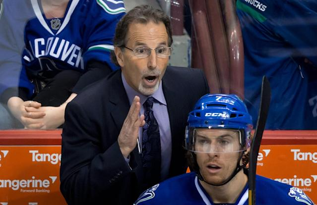 Vancouver Canucks' coach John Tortorella gives instructions to Ryan Kesler, not pictured, as David Booth sits on the bench during the third period of an NHL hockey game against the Colorado Avalanche on Thursday, April 10, 2014, in Vancouver, British Columbia. (AP Photo/The Canadian Press, Darryl Dyck)