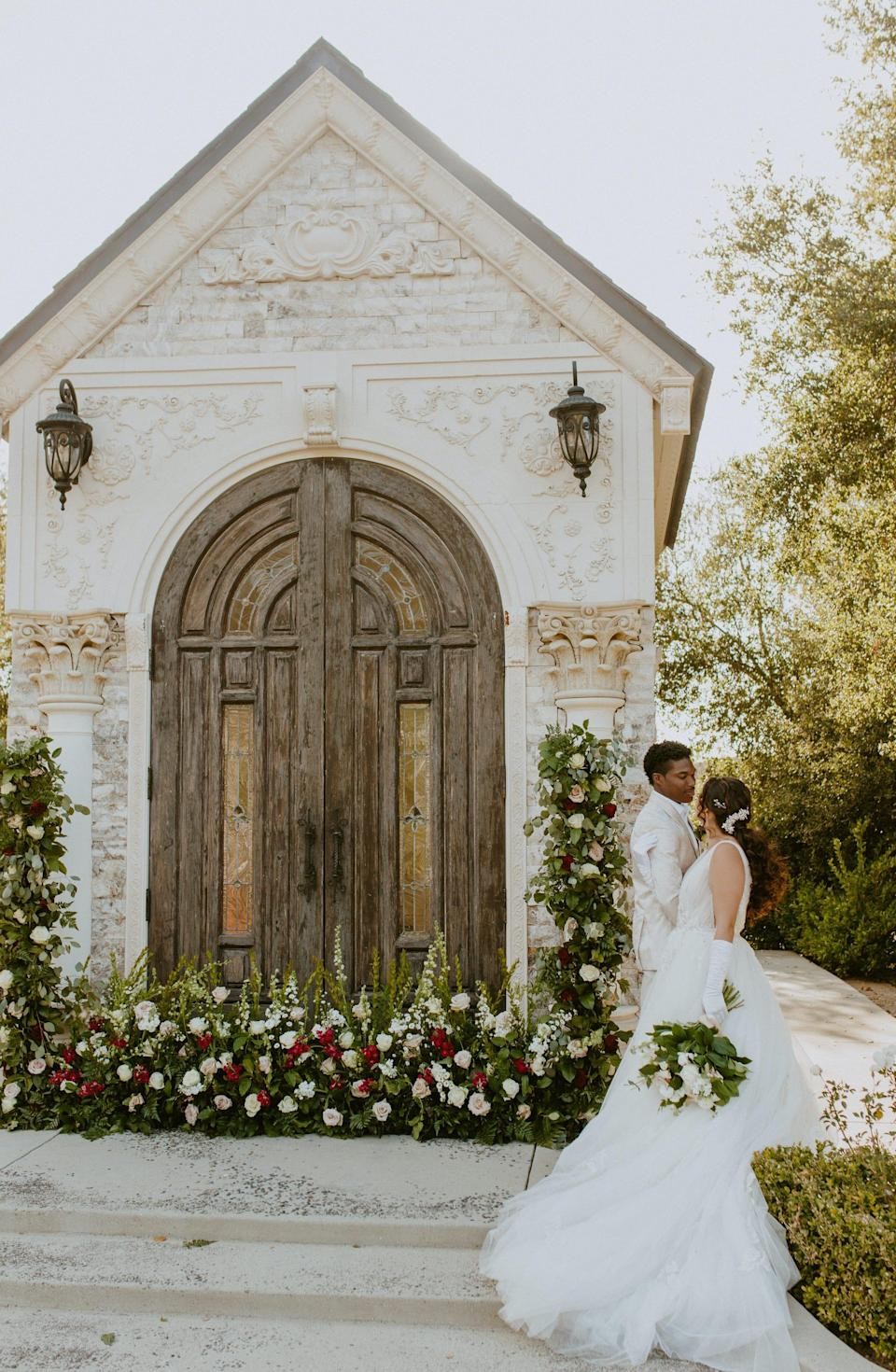 A bride and groom embrace in front of a chapel.