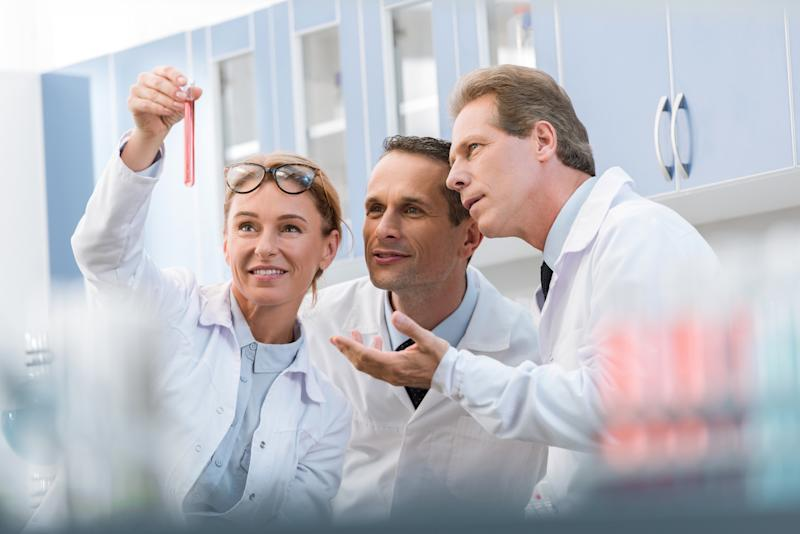 Three scientists discussing a pink test tube.