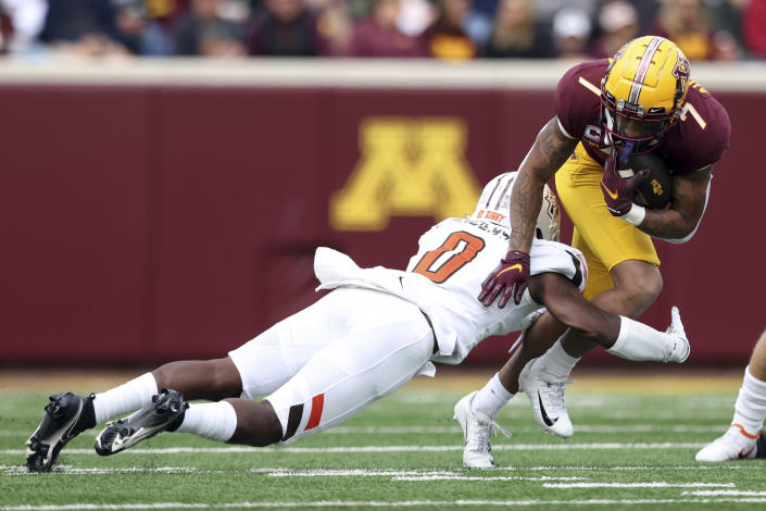 Minnesota wide receiver Chris Autman-Bell (7) is tackled by Bowling Green safety Jordan Anderson (0) during an NCAA college football game Saturday, Sept. 25, 2021, in Minneapolis. (AP Photo/Stacy Bengs)