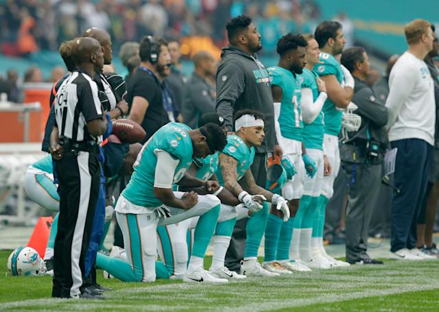 Dolphins players Kenny Stills, Michael Thomas and Julius Thomas kneel before their Sunday game in London, England.