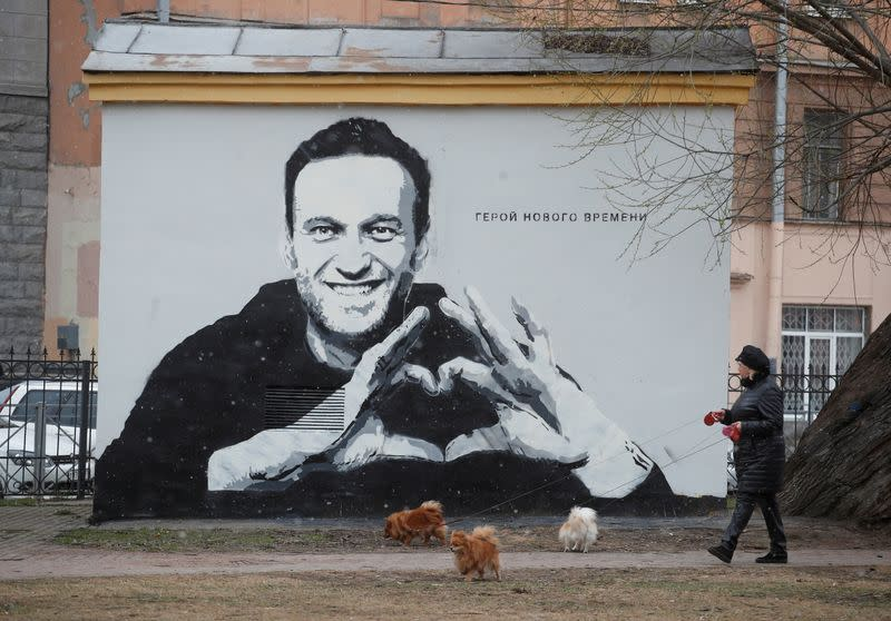 A woman walks her dogs in front of a graffiti depicting Alexei Navalny in Saint Petersburg