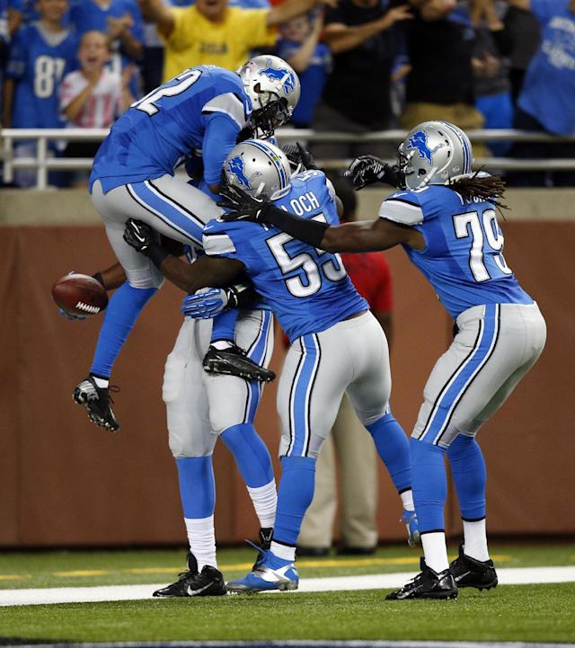 Detroit Lions defensive end Ezekiel Ansah is surrounded by teammates after his 14-yard interception return for a touchdown from New York Jets quarterback Mark Sanchez during the first quarter of an NFL football game at Ford Field in Detroit, Friday, Aug. 9, 2013. (AP Photo/Rick Osentoski)