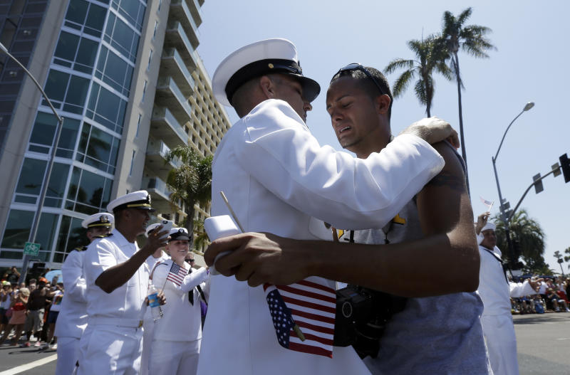 Navy Senior Chief Dwayne Beebe, center, embraces Jonathan Franqui, right, after proposing to him during the gay pride parade Saturday, July 21, 2012, in San Diego. For the first time ever, U.S. service members marched in a gay pride event decked out in uniform Saturday, after a recent memorandum from the Defense Department to all military branches made an allowance for the San Diego parade - even though its policy generally bars troops from marching in uniform in parades. (AP Photo/Gregory Bull)