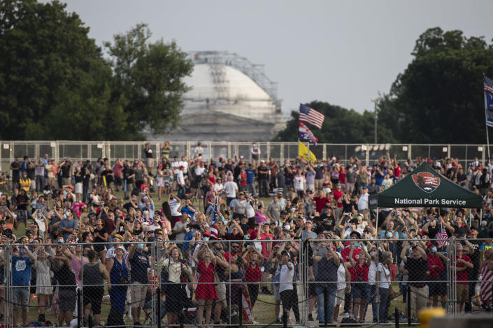 """Crowds watch flyovers from the National Mall during a """"Salute to America"""" event on the South Lawn of the White House, Saturday, July 4, 2020, in Washington. (AP Photo/Alex Brandon)"""