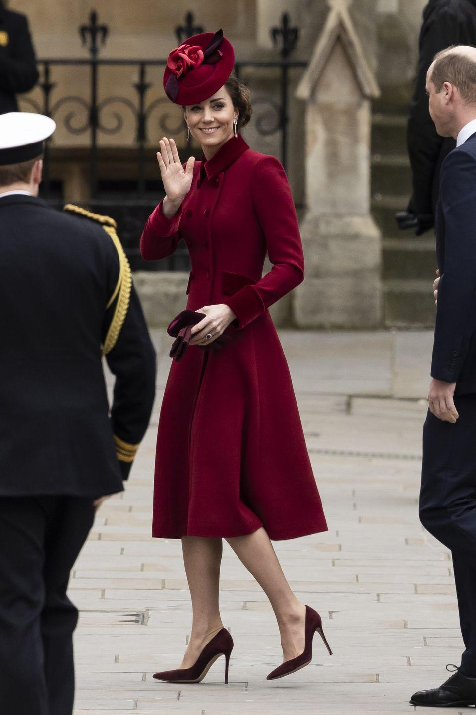 """<p>Kate chose a burgundy Catherine Walker <a href=""""https://www.townandcountrymag.com/society/tradition/a31139621/kate-middleton-red-coat-dress-commonwealth-service-photos/"""" rel=""""nofollow noopener"""" target=""""_blank"""" data-ylk=""""slk:coat dress"""" class=""""link rapid-noclick-resp"""">coat dress</a> for 2020's Commonwealth Day celebrations. She paired the elegant look (which she <a href=""""https://www.townandcountrymag.com/style/fashion-trends/a25634345/kate-middleton-red-coat-christmas-day-photos/"""" rel=""""nofollow noopener"""" target=""""_blank"""" data-ylk=""""slk:also wore on Christmas in 2018"""" class=""""link rapid-noclick-resp"""">also wore on Christmas in 2018</a>) with matching pumps and a red, floral hat. </p>"""