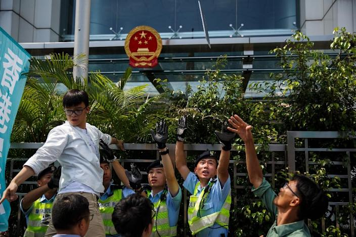 A pro-democracy group Demosisto member (R) throws a placard (top C) towards the Chinese Liaison office during a protest in Hong Kong on June 17, 2016 (AFP Photo/Anthony Wallace)