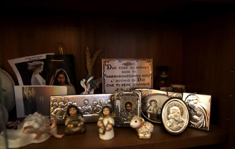 In this picture taken on Friday, Jan. 31, 2020 religious miniatures are displayed in a showcase at Yolanda Martinez Garcia's home, during an interview with the Associated Press, in Milan, Italy. Her son was sexually abused by one of the priests of the Legion of Christ, a disgraced religious order. (AP Photo/Luca Bruno)