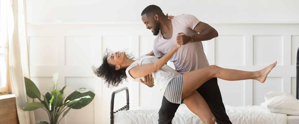 Cheerful active romantic couple wearing pajamas dancing in bedroom together,