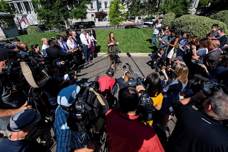 The closest journalists get to regular briefings from Sarah Sanders are impromptu gatherings outside the White House (AFP Photo/Jim WATSON)