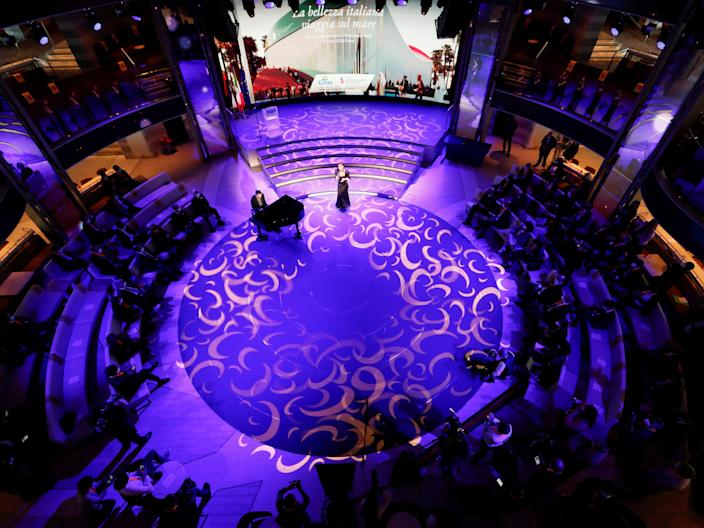 This image looks down on a purple circular stage with a singer standing in the top center and people sitting on the circle's outer rim.