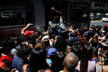 People try to get on a bus outside a closed metro station during a blackout in Caracas, Venezuela March 25, 2019. REUTERS/Carlos Garcia Rawlins
