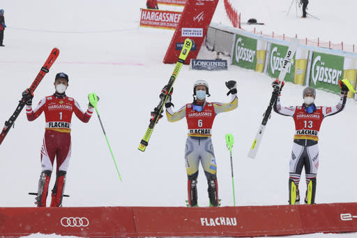 Norway's Sebastian Foss-Solevaag, center, the winner, is flanked by runner-up Austria's Marco Schwarz, left, and third placed France's Alexis Pinturault, after an alpine ski, men's World Cup slalom in Flachau, Austria, Sunday, Jan. 17, 2021. (AP Photo/Alessandro Trovati)