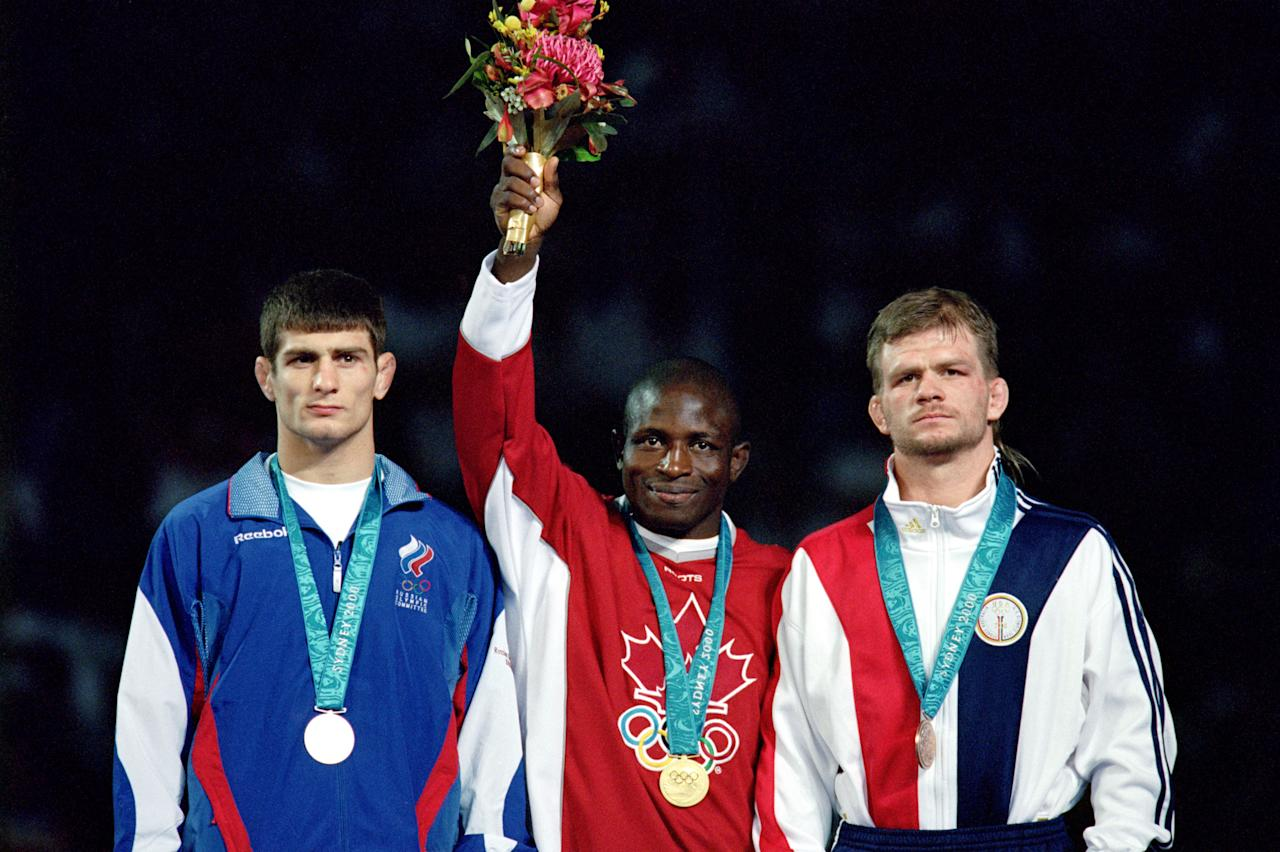 OCTOBER 10 - DARLING HARBOUR: (Left to Right) Arsen Gitinov (RUS-silver), Daniel Igali (CAN-gold), and Lincoln McIlravy (USA-bronze) are bestowed with Olympic medals in men's freestyle lightweight wrestling on October 10, 2000, at the Exhibition Hall in Darling Harbour, New South Wales, Australia, which was part of the 2000 Sydney Olympics. (Photo by Adam Pretty/Getty Images)