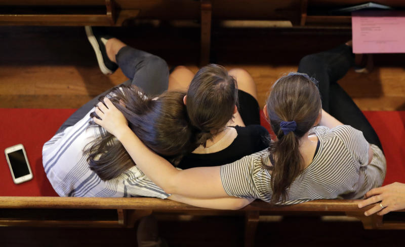 People comfort each other during a vigil at Fisk University to protest the execution of Billy Ray Irick Thursday, Aug. 9, 2018, in Nashville, Tenn. Tennessee carried out the execution of Irick, condemned for the 1985 rape and murder of a 7-year-old girl, marking the first time the state has applied the death penalty since 2009. (AP Photo/Mark Humphrey)