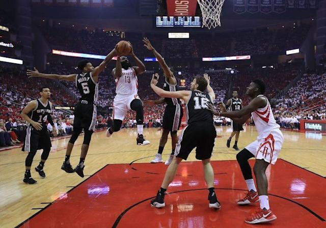 James Harden draws the attention of three Spurs defenders as he drives towards the rim. (Getty)