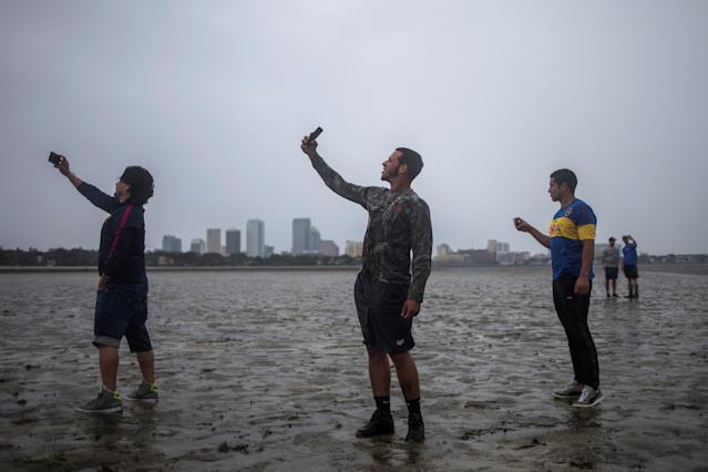 <p><strong>Tampa</strong><br>The Tampa skyline is seen in the background as local residents (L-R) Rony Ordonez, Jean Dejesus and Henry Gallego take photographs after walking into Hillsborough Bay ahead of Hurricane Irma in Tampa, Fla. on Sept. 10, 2017. (Photo: Adrees Latif/Reuters) </p>