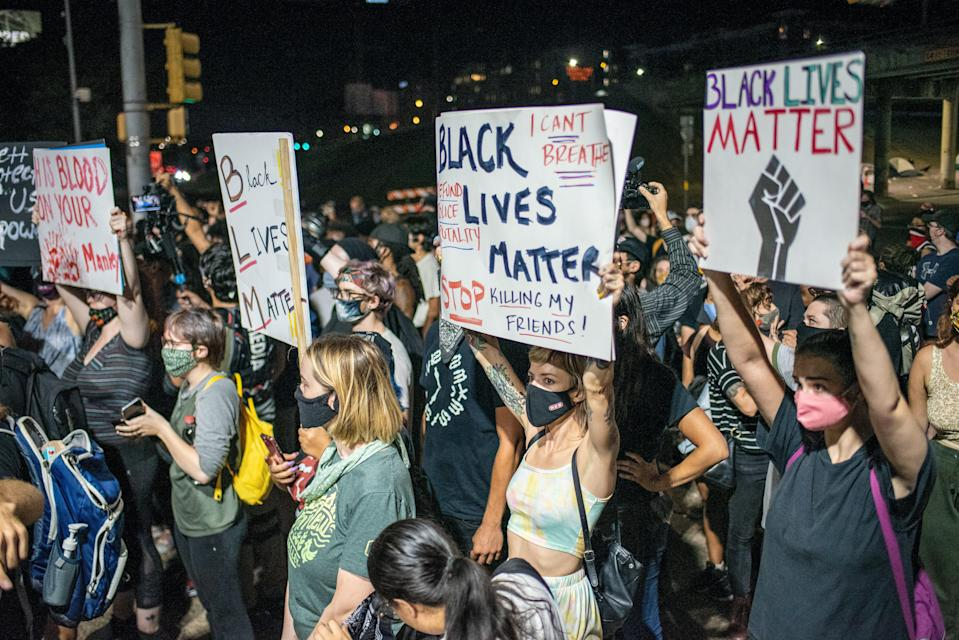 Demonstrators in Austin, Texas, hold up Black Lives Matter signs on 26 July, 2020. (Getty Images)