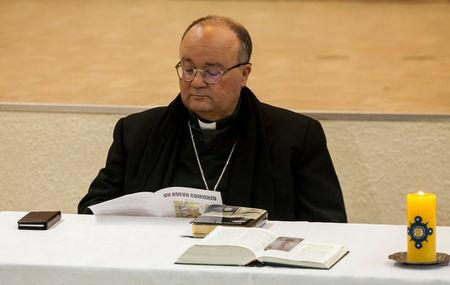 """Special Vatican envoys, archbishop Charles Scicluna reads a brochure  entitled """"A new beginning"""",  during a meeting with priests inside a church in Osorno"""