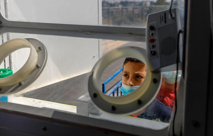 Image: A Palestinian child prepares to get checked for coronavirus at a mobile testing station in Sheikh Jarrah, Jerusalem on Monday. (Ahmad Gharabli / AFP - Getty Images)