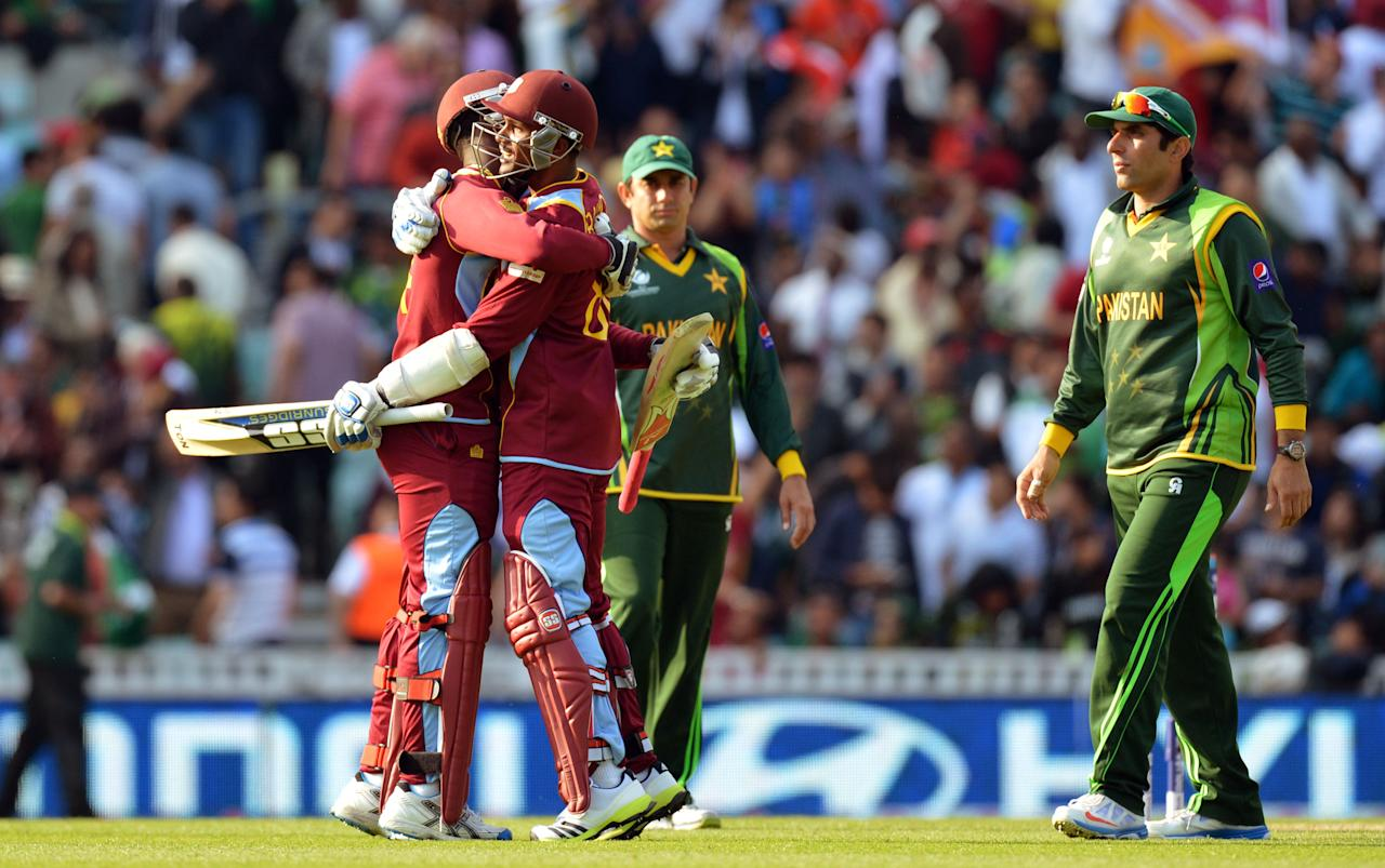 Pakistan's captain Misbah-ul-Haq (right) looks-on as West Indies' Kemar Roach (left) and Denesh Ramdin (right) celebrate their victory during the ICC Champions Trophy match at The Oval, London.