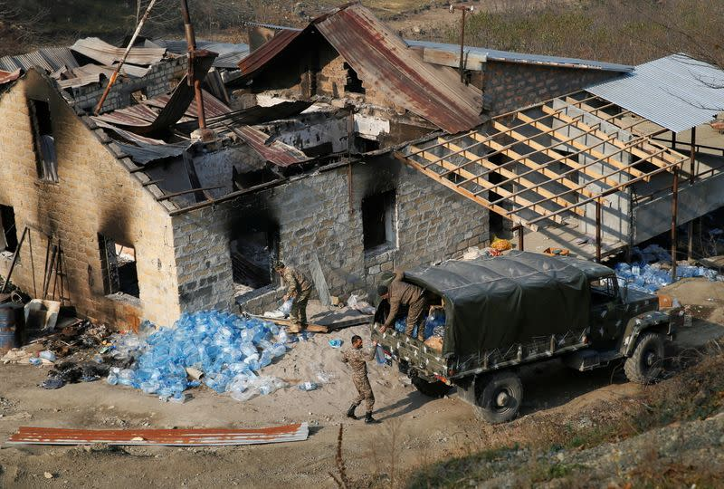 Ethnic Armenian soldiers load bottles with water into the truck in the village of Knaravan