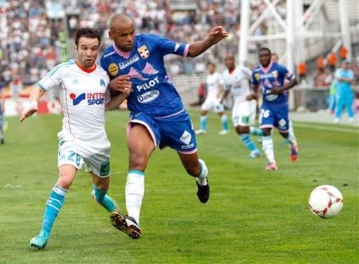 Marseille's French midfielder Mathieu Valbuena, left, challenges Evian's French defender Aldo Angoula for the ball during their League One soccer match at the Velodrome stadium, in Marseille, southern France, Sunday, Sept. 23, 2012. (AP Photo/Claude Paris)