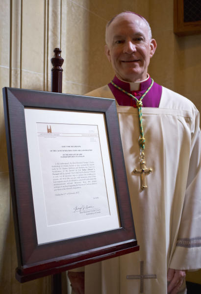 Omaha Archbishop George Lucas poses at St. Cecilia Cathedral in Omaha, Neb., Monday, Feb. 27, 2012, with a framed notice opening the cause for the beatification and canonization of Boys Town founder Father Edward Flanagan. (AP Photo/Nati Harnik)
