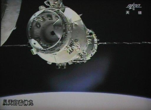 A photo of the giant screen at the Jiuquan space center shows the Shenzhou-9 spacecraft approching Tiangong-1 module for its automatic docking on Monday. Three Chinese astronauts on Monday entered an orbiting module for the first time, in a move broadcast live on China's state television network and a keystep towards the nation's first space station