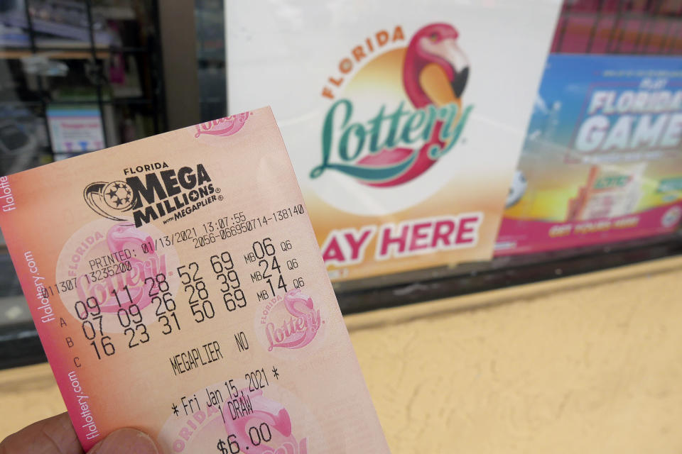 A customer shows off a Mega Millions lottery ticket after purchasing it, Wednesday, Jan. 13, 2021, in Orlando, Fla. Lottery players will have a shot Friday night at the fifth-largest jackpot in U.S. history after no tickets matched all the numbers in the latest Mega Millions drawing. (AP Photo/John Raoux)