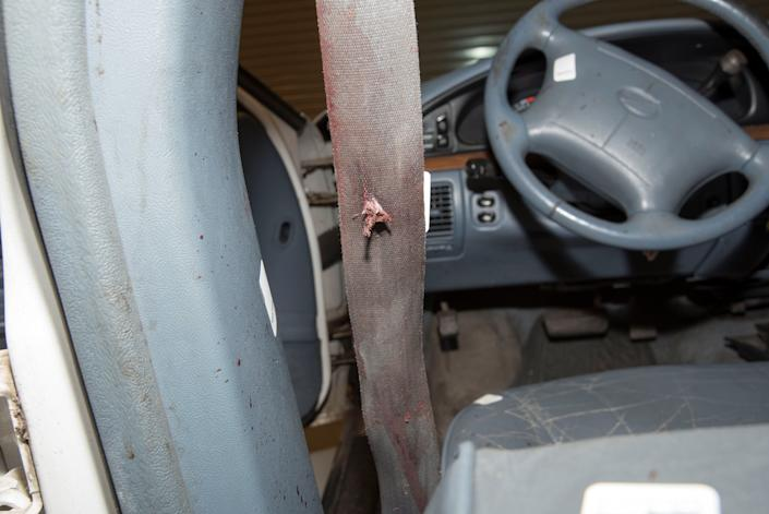 A bullet hole is seen on a bloodied seat belt.