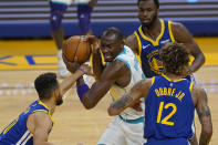 Charlotte Hornets center Bismack Biyombo, center, is defended by Golden State Warriors guard Stephen Curry, left, forward Andrew Wiggins, top, and guard Kelly Oubre Jr. (12) during the first half of an NBA basketball game in San Francisco, Friday, Feb. 26, 2021. (AP Photo/Jeff Chiu)